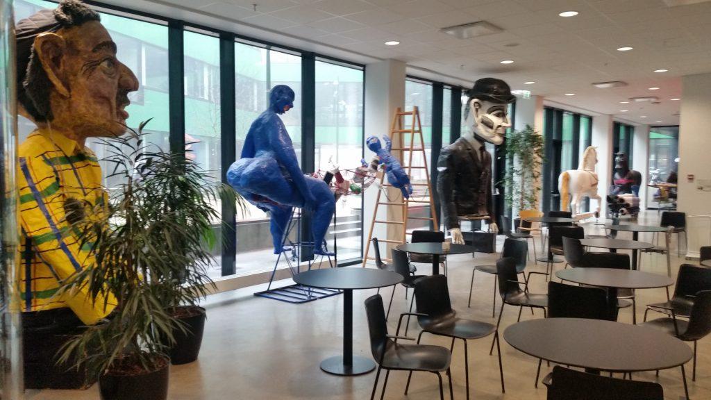 Kahvilamainen tila, jossa opiskelijoilla esimerkiksi teatteriesityksiä. Nuket heidän kansainvälisessä työpajassa tekemiään. Via Århus